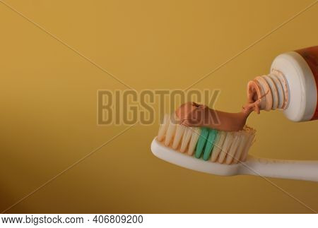 Toothbrush With Red Ayurvedic Toothpaste. Close Up Of Red Toothpaste Squeezed On Toothbrush On Clean