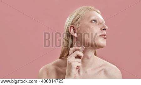 Young Caucasian Man With Long Blond Hair Massaging Neck Using Quartz Massager While Standing On Pink