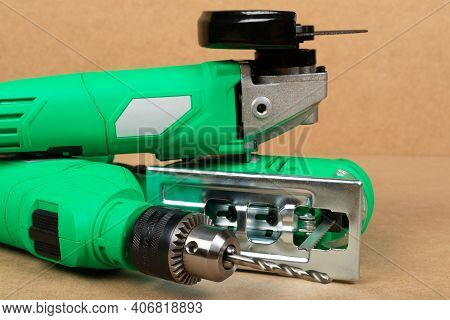 Picture Of A Green Jig Saw And A Drill  And  Angle Grinder On A Wooden Background