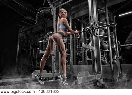 Leggy Girl Posing In The Gym. She Leaned On The Barbell. Back View. The Concept Of Sports, Bodybuild
