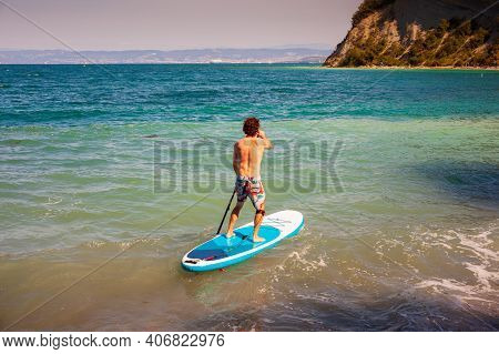 Stand Up Paddle Boarding. Joyful Man Is Training Sup Board In The Adriatic Sea On A Sunny Morning. S