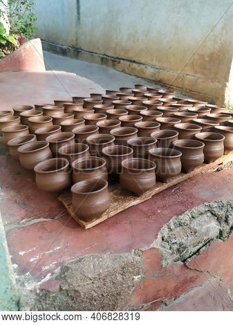 Wet Small Pot Holding In Hand And Group Pots In A Plate For Dry