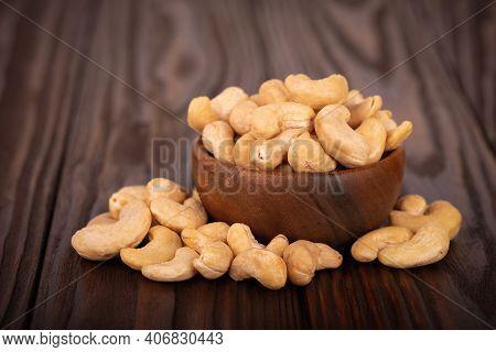 Cashew Nutsin Wooden Bowl, On Wooden Background. Roasted Cashew Nuts.