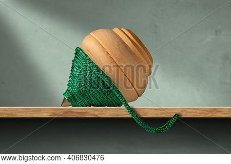 Close-up Of A Wooden Spinning Top With A Green Rope, On A Wood Shelf And Green Wall. Vintage Toy.