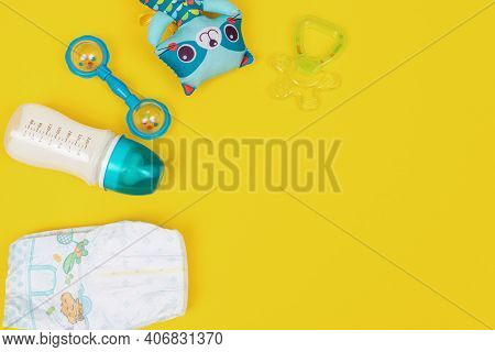 Bottle Of Baby Milk Formula With Teething, Diapers And Toys On Yellow Background. Flat Lay, Copy Spa