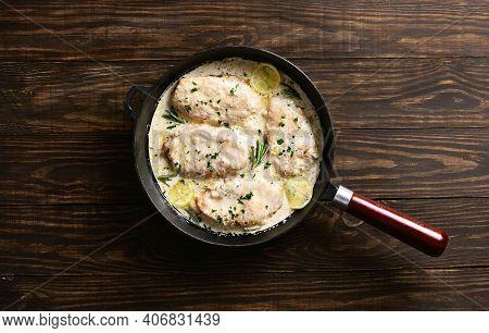 Chicken Or Turkey Breast In Creamy Garlic Sauce In Cast Iron Pan Over Wooden Background With Free Te