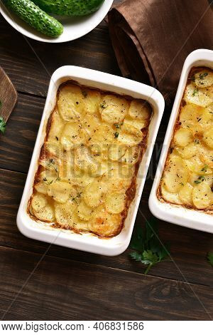 Potato Gratin In Baking Dish Over Wooden Background. Top View, Flat Lay