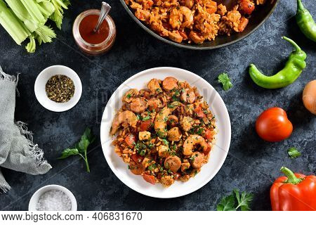 Creole Jambalaya With Rice, Prawn, Smoked Sausages, Chicken Meat And Vegetables On Plate Over Blue S