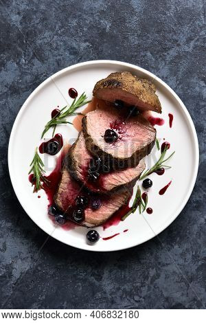 Sliced Grilled Beef With Blueberry Sauce On Plate Over Blue Stone Background. Tasty Medium Rare Roas