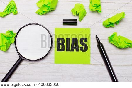 The Word Bias Written On A Green Sticky Note Next To A Magnifying Glass And A Black Marker On A Wood