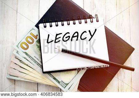 Legacy Text Written On Notebook With Dollar Bills And Pencil