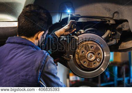 Mechanic Repairing Brakes On The Car. Mask. Selective Focus Disc Brake On Car.vehicle Repair Concept