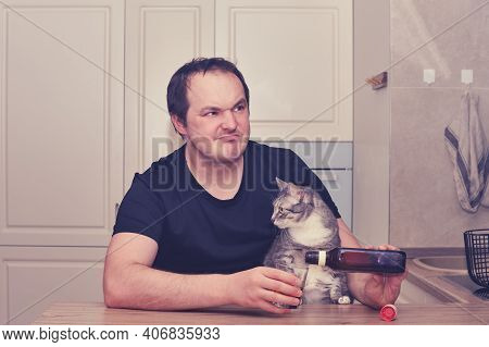 A Man Thoughtfully Drinks Alcohol Sitting In The Kitchen With A Cat And Reflects On The Problem. Alc