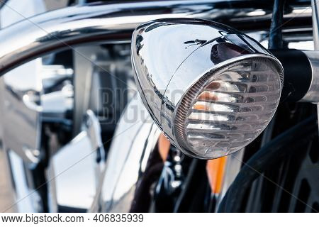 The Headlight Of A Powerful Road Bike With A Shiny Chrome Reflective Surface Of The Engine In The St