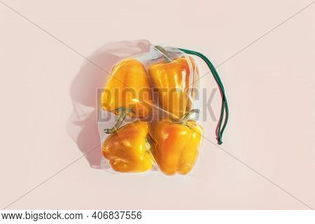 Reusable Packaging Of Products By Weight. Yellow Bell Peppers In A Reusable Bag On A Pink Background