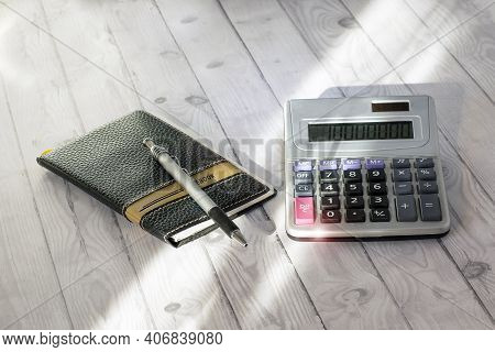 Closeup Of A Calculator, A Pencil And Notebook Arranged On A Table To Convey The Concepts Of Tax Sea