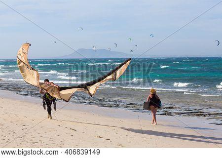 Fuerteventura, Spain - May 10, 2013. Kite Surfing Couple Walking On The Beach In Corralejo, Fuerteve