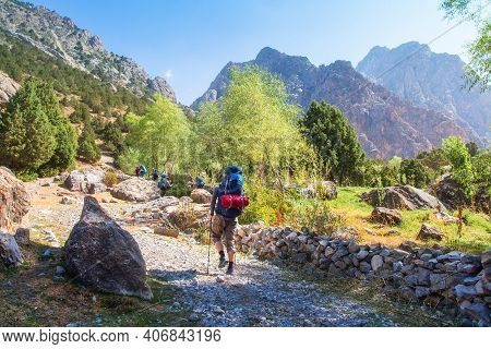 Group Tourists With Backpacks Hiking In Fann Mountains In Tajikistan. Hikers On A Mountain Trail In