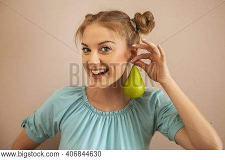Portrait Of Playful Cute Woman Holding Pear.toned Image.