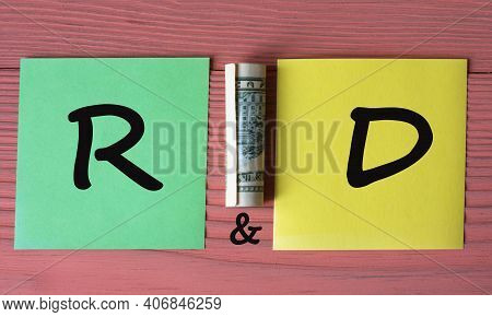 R And D (research And Development) - Acronym On Multicolored Pieces Of Paper On A Pink Wooden Backgr