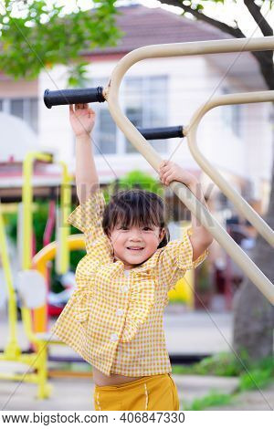 Vertical Portrait. Beautiful Little Girl Is Exercising. Asian Children Try To Reach Out To Hang On M