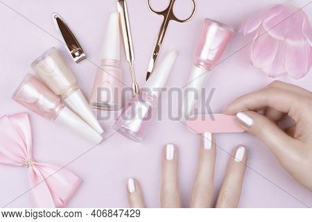 Female Fingers With Pastel Pink Manicure. A Woman Doing Herself A Pastel Pink Manicure. Manicure Too