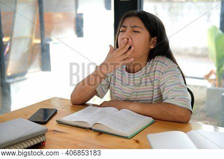 Girl Student Yawning While Reading Book Feeling Tired Bored Sleepy. Children Education