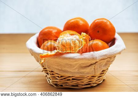 Tangerines (oranges, Clementines, Citrus Fruits) In A Wicker Basket Over Wooden Background With Copy