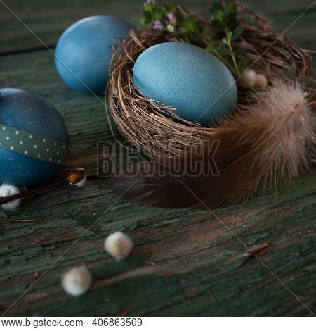 Happy Easter Background. Decoration With Blue Easter Eggs In A Nest With A Feather On Green Weathere