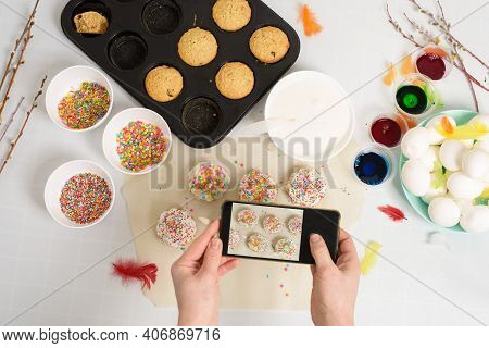 A Woman Takes Photos On Her Phone Of Mini Cupcakes Cakes For Easter With White Icing And Sweet Candi