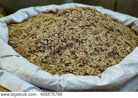 In Large Quantities Flattened Rice On A Village Market. Fresh Brown Flattened Rice Isolated Into The