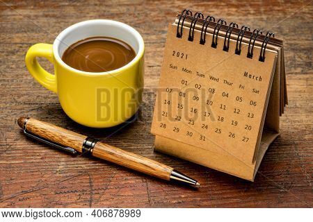 March 2021 - spiral desktop calendar against rustic weathered wood with a cup of coffee, time and business concept
