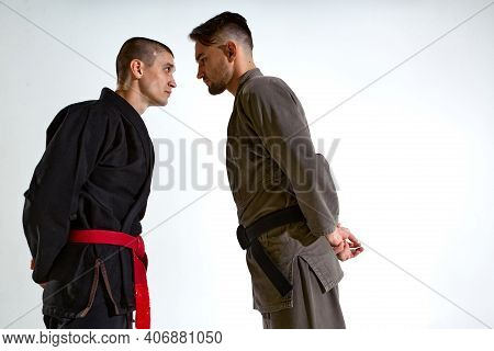 Guys In Kimono Face To Face Before Karate Fight Workout On White Studio Backdrop With Copy Space, Ma