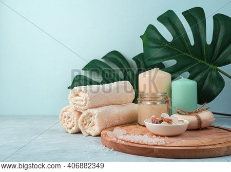 Spa Composition With Candles And Towels On A Light Blue Background With Monstera Leaves.