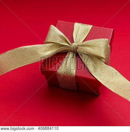 Red Gift Box With Gold Ribbon On Red Background, View From Above.