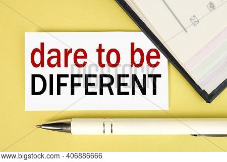 Dare To Be Different, Text On White Paper On A Yellow Background Near The Pen.