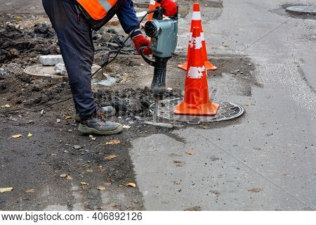 A Road Worker In A Reflective Orange Vest Smashes The Asphalt With An Electric Jackhammer Around A M