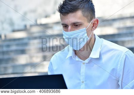 Young Businessman In Mask Working Outdoor On Laptop Computer. Pandemia And Coronavirus Concept