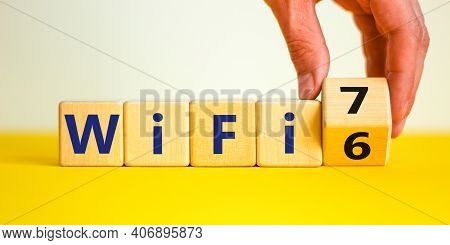 Wifi 6 Or 7 Symbol. Businessman Turns A Wooden Cube And Changes The Words Wifi 6 To Wifi 7. Beautifu