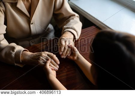 Young Granddaughter Taking Care Of Grandmother With Tender And Care. Wrinkled Hands Of Very Old Woma