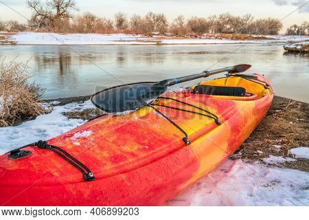 winter kayaking in Colorado - red whitewater kayak with a paddle on shore of St Vrain Creek