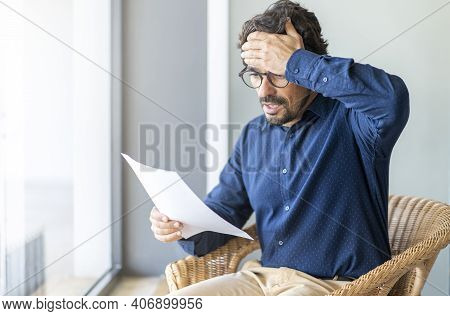 Casual Man Looking Surprised Reading Bills To Pay. Taxes, Bank Statement And Loan Debt. Male Portrai