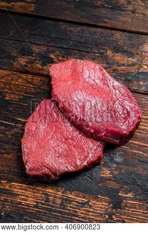 Raw Black Angus Beef Meat Sirloin Steak. Dark Wooden Background. Top View