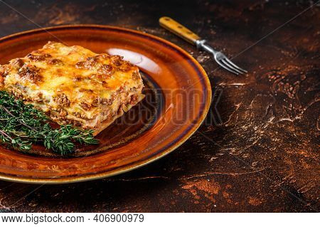 Italian Lasagne With Tomato Bolognese Sauce And Mince Beef Meat On A Rustic Plate. Dark Background.