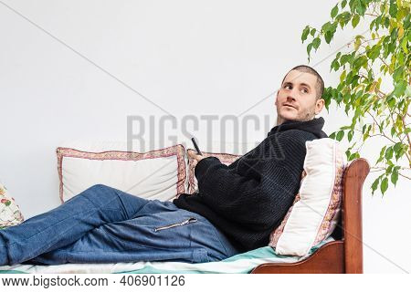 Relaxed Young Caucasic Man In Comfortable Clothes Lying On Comfortable Couch, Enjoying Spending Week