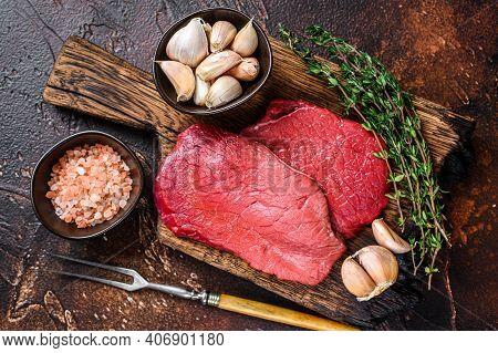 Raw Rump Beef Meat Steaks On Butcher Wooden Board. Dark Background. Top View