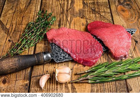 Black Angus Raw Beef Meat Sirloin Steak On Butcher Knife. Wooden Background. Top View