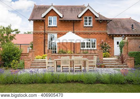 Large Luxury Detached House And Garden In Uk With Garden Furniture On A Patio In Summer