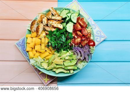Colorful Big Paleo Salad Bowl With Frilled Chicken Meat And Fresh Vegetables And Fruits On Colored W