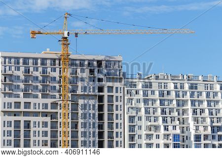 Tower Crane Construction On The Background Of A Completed Apartment Building And Blue Sky.  A Glut O